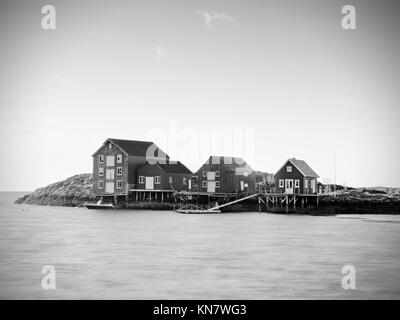 Traditional fishing village. Cottages at the coast on the rocky island. Red white building shinning in spring warm - Stock Photo