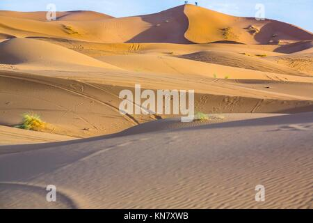 People admire the sunrise from a hill. Several sand hill at Erg Chebbi in the Sahara desert. Ers are large dunes formed by wind-blown sand.