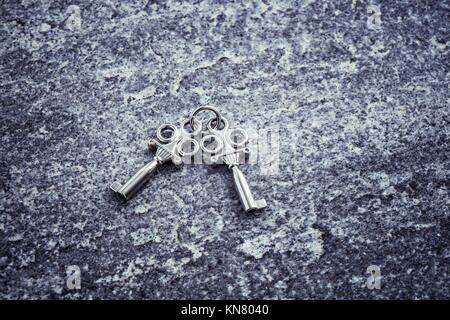 Two old vintage keys lying on stone table. Concept of business success, safety or retro objects. Symbol of romantic - Stock Photo