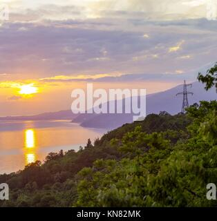 Overhead power transmission line in mountains with sea and sunset on background, Russia, Caucasus - Stock Photo