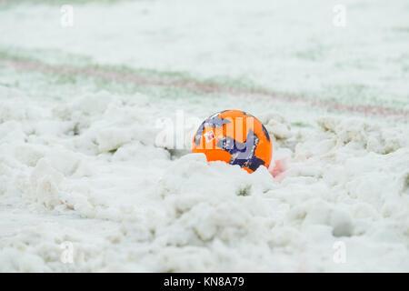 Koeln, Deutschland. 10th Dec, 2017. Ein oranger Fussball liegt im Schnee, Feature, allgemein, Randmotiv, Fussball - Stock Photo