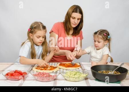 Mom helps younger daughter spread ketchup on a pizza, the eldest daughter, she is preparing a second pizza. - Stock Photo