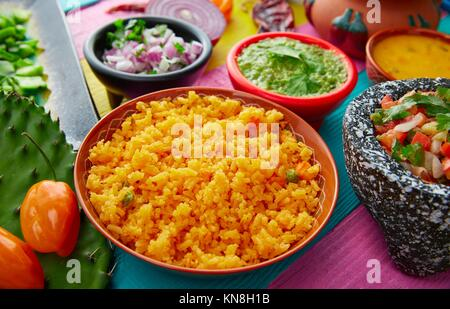 Mexican yellow rice with chilis and sauces in colorful background. - Stock Photo