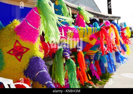 Mexican party pinatas decorated with fringed tissue colorful paper. - Stock Photo
