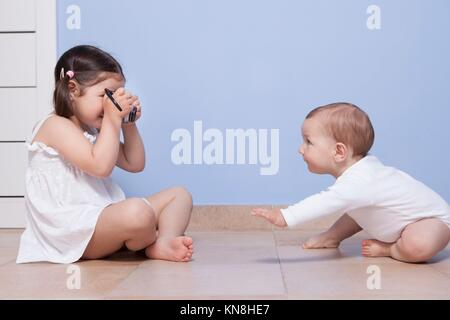 Young girl photographer. Pretty little sister taking pictures to her baby brother with old analog camera. - Stock Photo