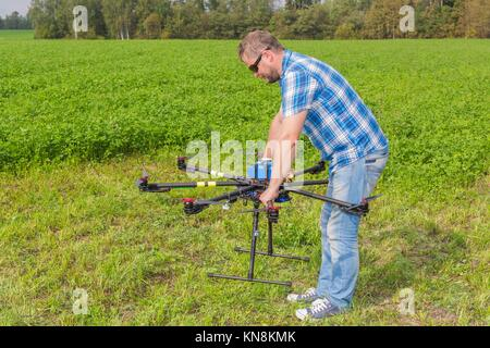 Technician holding multicopter in hands pilot copter. - Stock Photo