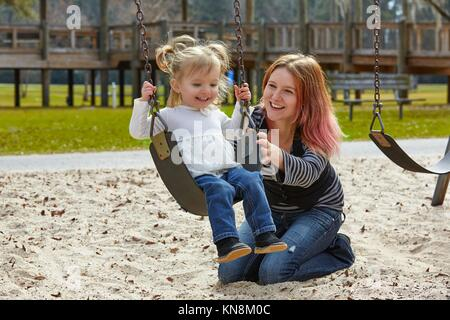 Mother and daughter in a swing having fun at the park playground. - Stock Photo
