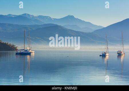 Anchored yachts at misty morning on the lake on mountains background, Fethiye, Mugla Province, Turkey - Stock Photo