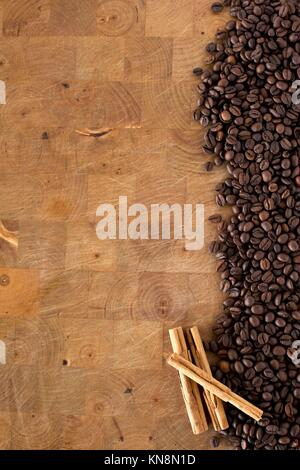 Detail of a pile of coffee beans and cinnamon background. - Stock Photo