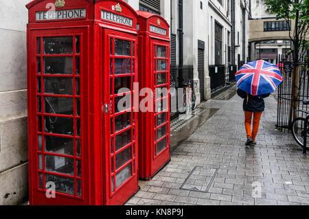 Telephone Box, Women with Umbrella, Raiun, London - Stock Photo