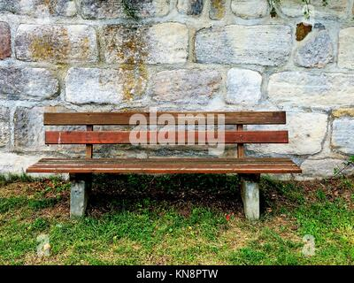 old abbey wall with park bench. - Stock Photo