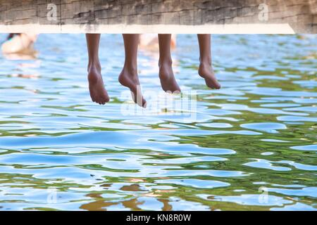 Boy´s Legs Dangling Down from Wooden Pier over Water. - Stock Photo