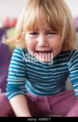 portrait of blonde two years old child with striped blue and white sweater sitting and crying looking. - Stock Photo