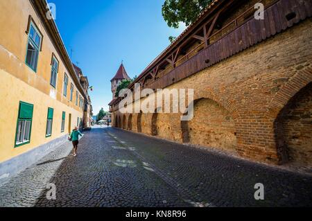 Street with Carpenter's Tower on background in Sibiu city in Romania. - Stock Photo