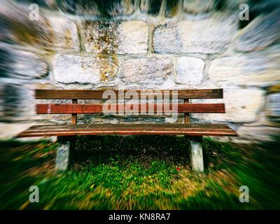old abbey wall with park bench in retro view. - Stock Photo