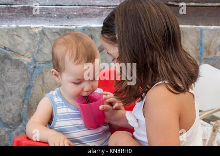 Little sister helping to her baby brother to drink juice with straw. She is holding the plastic glass. - Stock Photo
