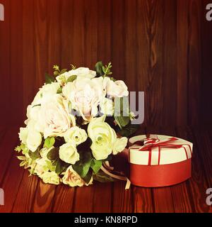 Beautiful wedding bouquet from white and pink roses with retro filter effect on wooden background. - Stock Photo