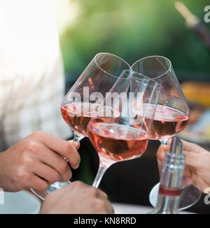 Happy friends having fun outdoors, Focus on hands toasting rose wine glass during barbecue. - Stock Photo