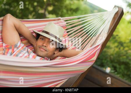 Man Sleeping and Relaxing With hat In Hammock, France. - Stock Photo