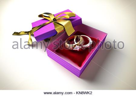 Opened gift box with golden ribbon, with two precious rings, on a red pillow inside. - Stock Photo