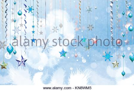 Christmass abstract background with several decorations hanging down in foreground. Light blue dominant color. Some - Stock Photo