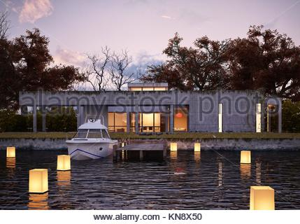 Luxury modern house on water at sunset, with private peer and yacht. Glowing lights floating on water give spacial - Stock Photo