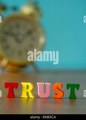 Trust. English alphabet made of wooden letter color. Alphabet trust on wooden table and vintage alarm clock and - Stock Photo