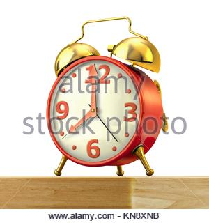 Classic alarm clock with red body and golden bells, on a wood table and white background, close up view. Clipping - Stock Photo
