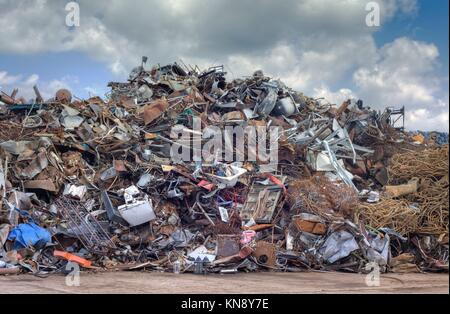 Iron Raw Materials Recycling Pile over Cloudy Sky. Metal Waste Junkyard. - Stock Photo