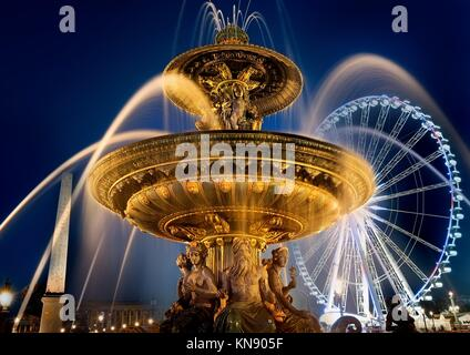 Fountain of Mars and ferris wheel on square of Concorde in evening Paris, France. - Stock Photo