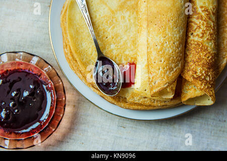 Stack of Rolled Golden Crepes on White Plate Black Currant Jam in Crystal Rosette Spoon Linen Tablecloth Top View - Stock Photo