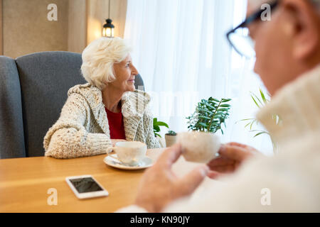 Pensive Senior Woman at Table in Cafe - Stock Photo