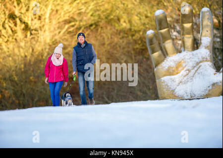 Couple walking with a young Whippet dog with the Golden hand sculpture in the backgroung. - Stock Photo