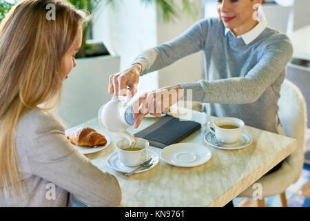 Two Young Women Enjoying Breakfast in Cafe - Stock Photo