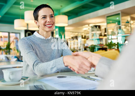 Businesswomen Shaking Hands in Cafe Meeting - Stock Photo