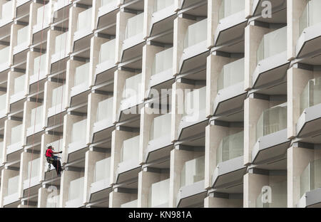 Workman painting hotel in Spain - Stock Photo