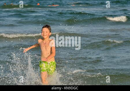 boy running through the waves at the beach. - Stock Photo
