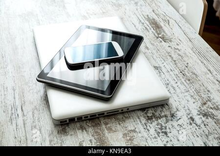 A smartphone, a tablet computer and a laptop computer on a wooden desktop.. - Stock Photo