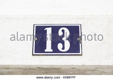 Number thirteen on a wall in a house, detail of a wall with a figure on a plate. - Stock Photo
