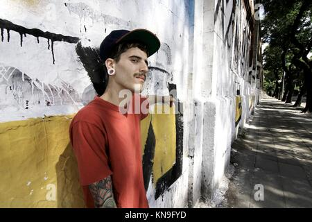 A young Rapper leaning against a wall. - Stock Photo