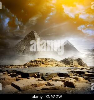 Orange storm clouds and fog over egyptian pyramids. - Stock Photo