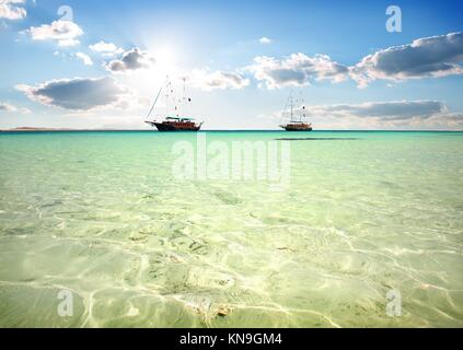 Two sailboats in turquoise sea under sunlight. - Stock Photo