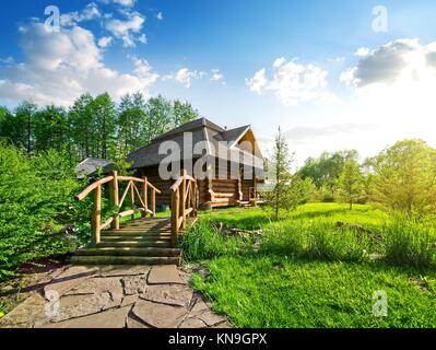 Wooden bridge and house of log in the forest. - Stock Photo