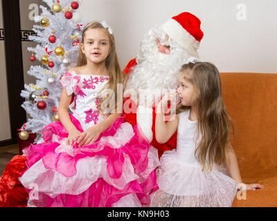 The older girl is sitting on the lap of Santa Claus and tells poem. - Stock Photo