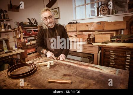 leather goods craftsman at work in his workshop, France. - Stock Photo
