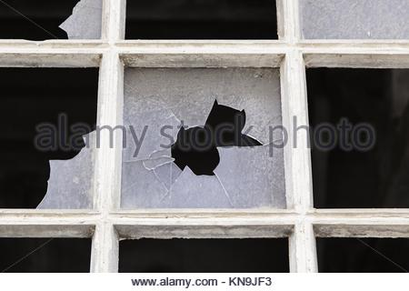 Old window with broken glass, detail of an abandoned factory, ruin and crime in Spain - Stock Photo