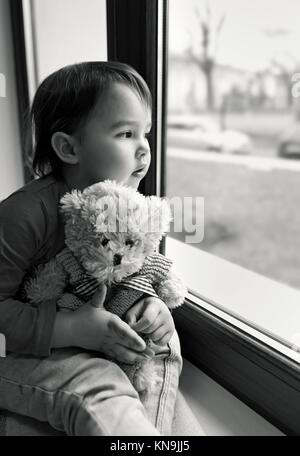 Little girl looking out the window at home. - Stock Photo