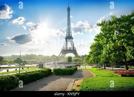 Eiffel tower near green park in Paris, France. - Stock Photo