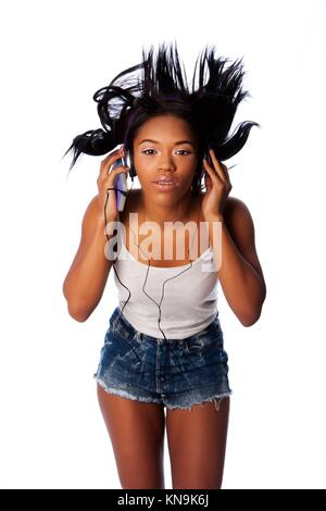 Beautiful teenager jamming listening to music with wild hair, on white.