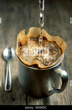 Ground coffee in filter holder isolated on wooden background. - Stock Photo